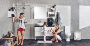 Iloinen äiti, pikkulapsi ja isä kylpyhuoneessa. Pieni hyllykkö seinällä. Valkoiset kylpyhuoneen kaapin ovet.