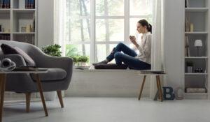 Nainen istuu kahvikuppi kädessä olohuoneen ikkunan edessä olevalla istumatasolla. Olohuoneessa on valkoinen istuintaso tai penkki, valkoiset hyllyköt ja kapea korkea hyllykkö.